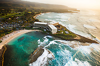 Big waves touch the shores of Turtle Bay Resort at sunset, with Kawela Bay in the distance, O'ahu.