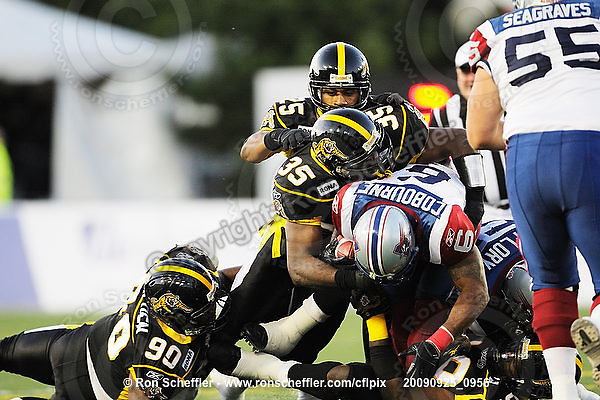 September 25, 2009; Hamilton, ON, CAN; Hamilton Tiger-Cats linebacker Otis Floyd (35) tackles Montreal Alouettes running back Avon Cobourne (6). CFL football: Montreal Alouettes vs. Hamilton Tiger-Cats at Ivor Wynne Stadium. The Alouettes defeated the Tiger-Cats 42-8. Mandatory Credit: Ron Scheffler. Copyright (c) 2009 Ron Scheffler.