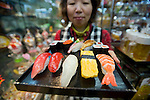 Akiko Sato carries replica sushi, which are placed in the windows of restaurants throughout Japan but have become popular souvenir items with foreigners, at her store, Sato Food Sample Co., in Kappabashi, Tokyo, Japan on November 19, 2010. Often called Tokyo's Kitchen Town, stores in Kappabashi still mainly caters to professionals in the catering industry, though is becoming increasingly popular with foreigners hunting for unique souvenirs.. Photographer: Robert Gilhooly