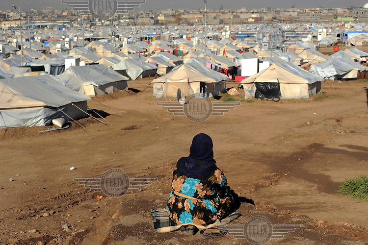 An elderly woman sits on a hillside overlooking the tents at the Kawergosk Syrian Refugee Camp.