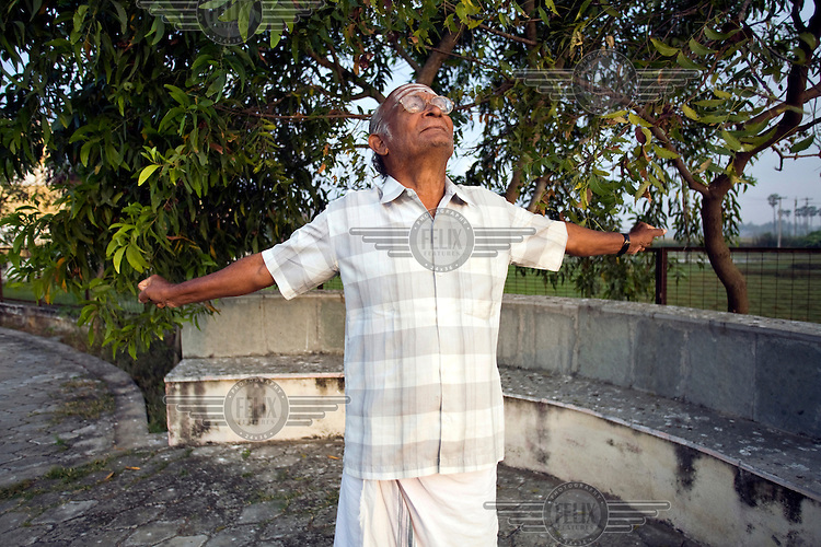 An elderly resident stretches and takes the morning air at dawn by the lake at the Tamaraikulam Elders' Village. The village is a pioneering experiment initially set up by HelpAge India after the Asian Tsunami to help elderly people displaced by the natural disaster. Today, the village is a self-sustaining community providing a family environment where more able-bodied residents assist the less able-bodied and provides 100 older people with a safe place to live, free healthcare, emotional security, a good diet and professional care and support...