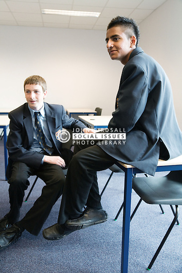Secondary school students taking time out to chat in a classroom,