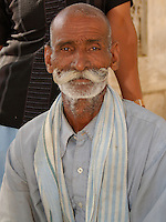 Man with mustache waiting to be seen outside the clinic at Fort Dundlod, India.