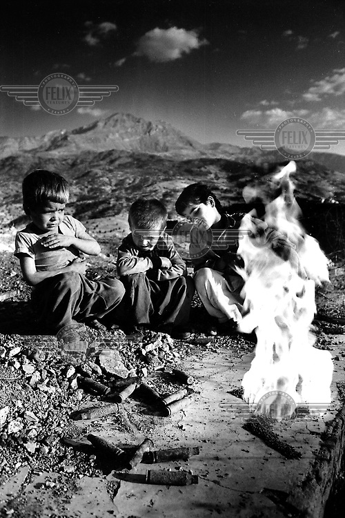CHOMAN, KURDISTAN, IRAQ, OCTOBER 1993. Young children break open ammunition and set fire to the powder. Twenty million landmines and unexploded ordnance litter the former frontline in the Iran vs Iraq War still killing and maim ing Kurdish people on a daily basis.©Photo by Frits Meyst/Panos Pictures
