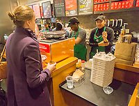 Starbucks baristas busy making espresso drinks during the first day of the Starbucks Cheer promotional event in New York on Friday, December 23, 2016. For the next 10 days, excluding Christmas, Starbucks is giving away a tall espresso drink of your choice between the hours 1 and 2PM at a rotating choice of 100 stores around the country. (© Richard B. Levine)