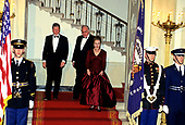 United States President Bill Clinton, left, Chancellor Helmut Kohl of Germany, center, and first lady Hillary Rodham Clinton, right, descend the Grand Staircase of the White House in Washington, DC prior to posing for a photo prior to an Official Dinner in the Chancellor's honor on Thursday, February 9, 1995.  The portrait in the background is the official portrait of former US President Ronald Reagan.<br /> Credit: John Harrington / Pool via CNP