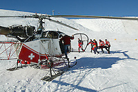 Switzerland. Valais. Crans Montana. Winter ski resort. A group of  Swiss Ski School teachers carry an injured person on a shaft. Medical emergency. The wounded person will be air lifted by an helicopter from Air Glaciers. Swiss flag. Blue sky on a sunny day. © 2005 Didier Ruef