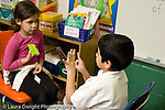 Education Elementary school Grade 1 mathematics boy and girl doing addition problems using flash cards and fingers horizontal