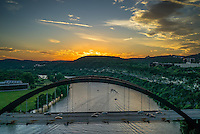 This is an aerial image of the Austin 360 Bridge as the sunset on Lake Austin.  You can see the bridge with the water below as the sky lights up with color.