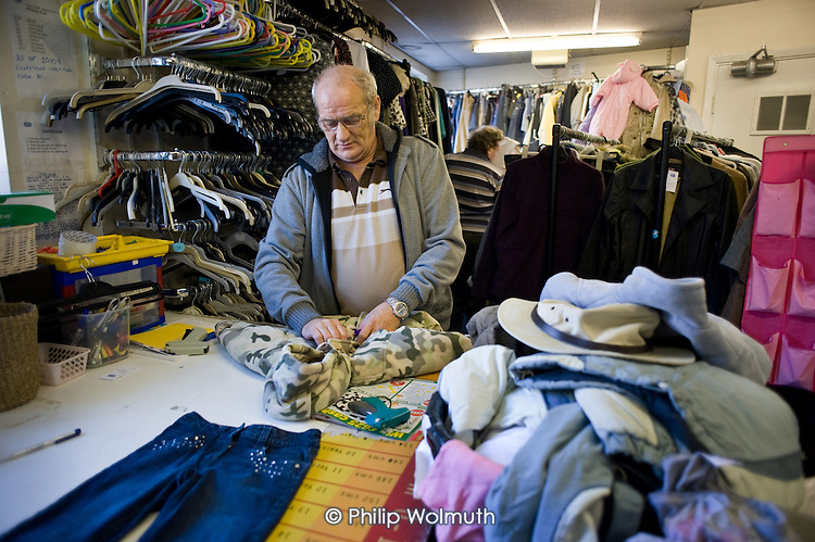 A Job Seekers Allowance claimant on a compulsory four week unpaid work placement in an RSPCA charity shop in Middleton, Rochdale, part of a Mandatory Work Related Activity welfare-to-work programme.