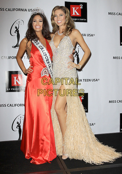 NICOLE JOHNSON, Miss California 2010 & TAMI FARRELL, Miss California USA 2009.Miss California 2010 Pageant Finals held Agua Caliente Casino Resort Spa, Palm Springs, California, USA..November 22nd, 2009.full length pink red silk satin dress gown crown tiara winner sash silver white beige slit split feather hand on hip .CAP/ADM/KB.©Kevan Brooks/AdMedia/Capital Pictures.