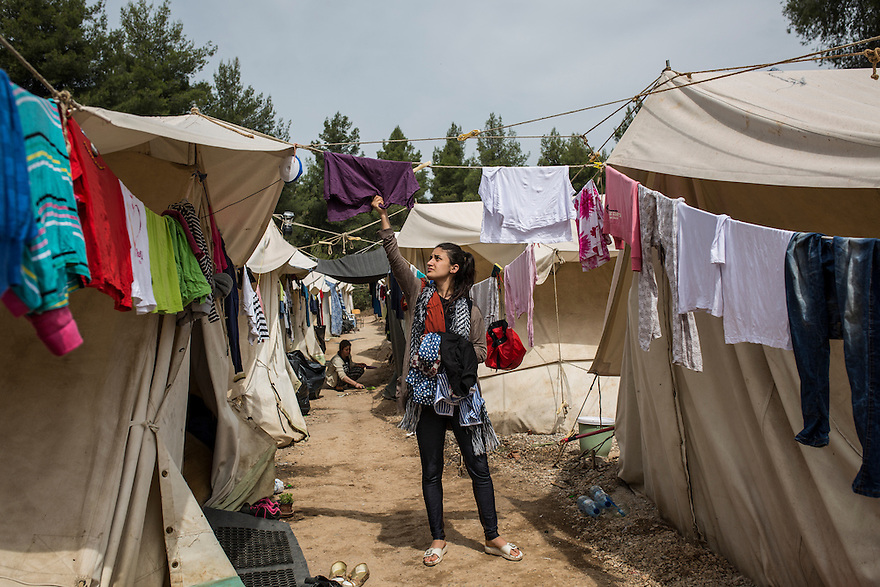 Collecting laundry next to the tents where the Noh family are living at Ritsona Camp. The family are Yazidi and immigrated from Iraq due to the ISIS threat nearby. PHOTO BY JODI HILTON/PULITZER CENTER