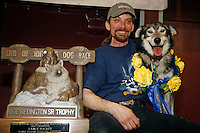 "2007 Iditarod champion Lance Mackey and his lead dog ""Larry"" pose with the first-place ""Joe Redington Sr."" trophy at the Nome awards banquet."