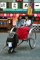Asakusa Rickshaw with Japanese women tourists having a photo op with the rickshaw puller.