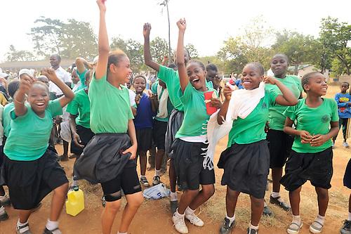 Girls on the sideline celebrating a goal by their soccer team in Likoni, Kenya