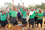 Girls on the sideline celebrating a goal by their soccer team in Likoni, Kenya