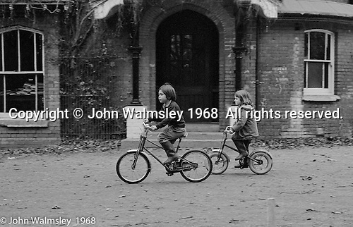Little kids cycling passed the main building, Summerhill school, Leiston, Suffolk, UK. 1968.
