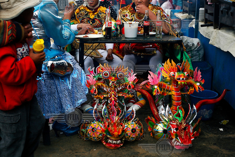 Dancers dressed in devil costumes eat lunch at the Carnaval de Oruro. During the fiesta many people sacrifice llamas and give offerings such as coca leaves and cigarettes to show their dedication to the Devil, a Virgin, Pachamama or Mother Earth. The Devil (or Uncle) is a mythical character that protects the miners of Oruro who work in dangerous conditions hundreds of metres below the ground. During the carnival, people dress in outrageous costumes and dance for days before arriving at the Church of Socavon, where they pay their respects to a virgin. Ironically, many of the dancers wear devil costumes.