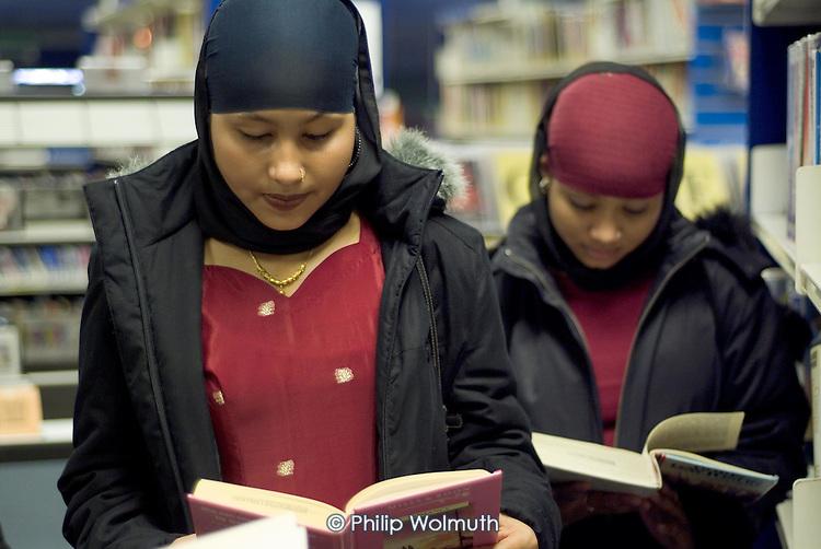 Young Bangladeshi women read books in Church Street Library, Paddington, London.