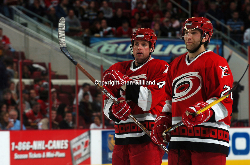 Carolina Hurricanes' Erik Cole (26) and Aaron Ward (4) discuss things prior to a faceoff during a game with the Tampa Bay Lightning Sunday, Nov. 20, 2005 in Raleigh, NC.  Tampa Bay won 5-2.