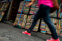 A Salvadoran woman walks along hundreds of used books stacked in boxes on the street in a secondhand bookshop in San Salvador, El Salvador, 12 April 2018. Large collections of worn-out books, mostly textbooks and educational paperbacks, are sold regularly in secondhand bookshops in the center of the city.