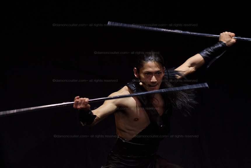 A performer on stage during the Mangekyo performance by Wadaiko group, DRUM TAO in Lumine 0 theatre, Shinjuku, Tokyo, Japan, Friday November 16th 2018. The Mangekyo  performance includes koto and shamisen music along with traditional  and contemporary taiko drumming and acrobatics. Organised by the Japan Tourist bureau (JTB) and the Japanese Government to entertain foreign visitors in readiness for the 2020 Tokyo Olympics. the performances run to the end of November and utilise state of the art projection mapping by TeamLab.