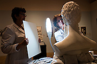 """Conservators Rika Smith McNally (left) and Regina Gaudette work on a replacement nose for a bust of abolitionist John Brown in the Tisch Family Gallery at the Tufts University Art Gallery at Tufts University in Medford, Massachusetts, on Thurs., Oct. 6, 2016. The bust was sculpted by Edward Augustus Brackett and had been improperly stored for decades with a broken nose and eyebrow. The conservators, from Rika Smith McNally and Associates, found a plaster cast made from the original at the Boston Athenæum and had a 3D modeler image the broken section of the original and the cast. They then used 3D printing technology to use to create a plaster nose replacement that would fit perfectly on the broken marble bust. They then used gouache paint to match the replacement pieces to the original marble.  The bust is part of an exhibition at the gallery entitled """"Mortal Things: Portraits Look Back and Forth."""""""