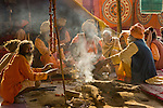 A sect of Sadhus socializes around a morning fire at the Kumbh Mela celebration.