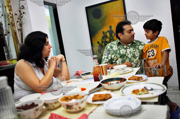Raman Verma, middle, eats brunch with his wife Payal and son Shaurya at their house. Raman attended a cooking class the day before in an effort to improve the family's nutrition which depends heavily on take-out, fried and fatty foods. As new processed foods have become available in India to the wealthy and upper middle classes, obesity rates have soared. These classes are now beginning to realize that newer, modern, imported foods are not necessarily better or healthier for them than traditional Indian food.