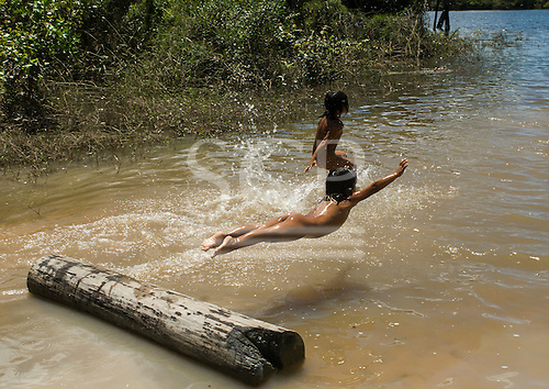 Xingu Indigenous Park, Mato Grosso State, Brazil. Aldeia Yawalapiti. A girl flying through the air, diving into the water.