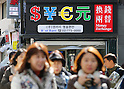 Exchange rate, Mar 12, 2015 : People walk past a currency exchange in central Seoul, South Korea. The Bank of Korea brought down the base rate to a record low of 1.75 percent on Thursday leading to a weakening of the Won.  (Photo by Lee Jae-Won/AFLO) (SOUTH KOREA)