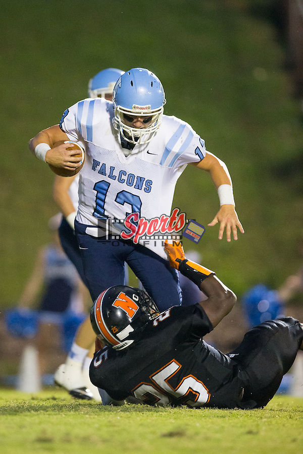 Harrison Baucom (13) of the West Rowan Falcons is pulled down by Anthony Caldwell (25) of the Northwest Cabarrus Trojans at Trojan Stadium September 19, 2014, in Concord, North Carolina.  The Falcons defeated the Trojans 13-0.  (Brian Westerholt/Sports On Film)