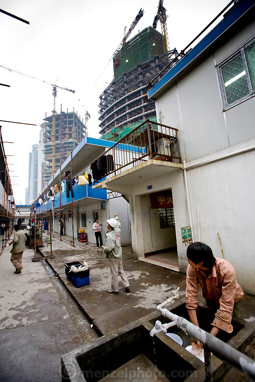A sky scrapper under construction looms above the rows of dormitories in which Huang Neng shares a room with nine other workers in Shanghai, China. (Huang Neng is featured in the book What I Eat: Around the World in 80 Diets.)