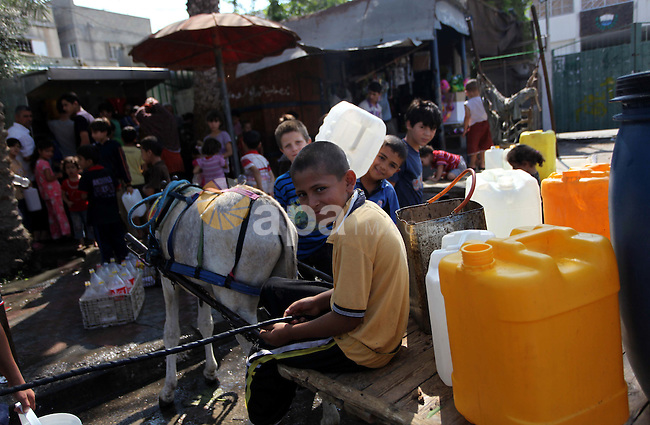 Palestinians children fill plastic bottles and water containers with drinking water from a public tap in Jabalia in the northern Gaza Strip on July 27, 2014. Three Palestinians were killed in shelling as the Israeli military resumed its assault on Gaza after Hamas shunned an extended lull accepted by Israel, medics said. Photo by Ashraf Amra