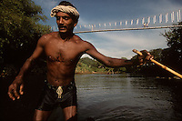 A Sri Lankan man poles his barge up river as workers manually transport dirt from the river bed in 1996.