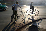 Bicyclists pass through the morning haze of diesel exhaust left by morning traffic in Havana, Havana Province of Cuba, on Jan. 16, 2004.