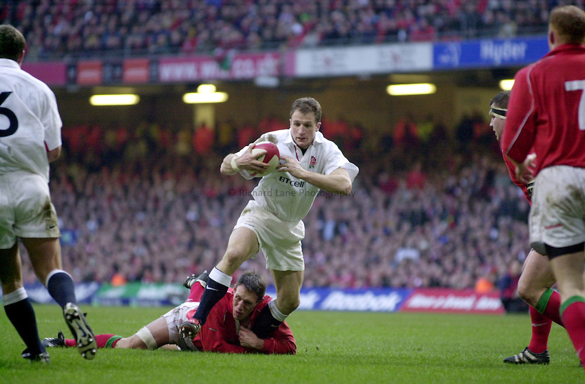 Photo Richard Lane..Wales vs England. .Lloyds T.S.B Six Nations Championship 2001..Millenium Stadium, Cardiff. 03.02.2001.Mike Catt trys to squirm away from the tackle of Mark Taylor..