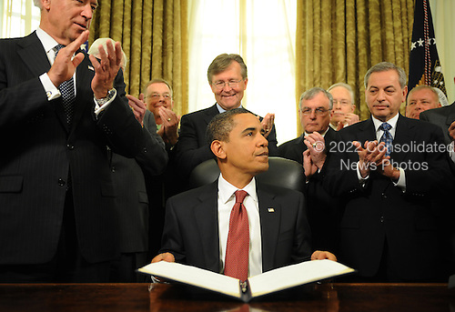 Washington, DC - January 22, 2009 -- United States President Barack Obama (C) is applauded by Vice President Joseph Biden (L) and a group of retired military officers after he signed the third of four executive orders to close the Guantanamo Bay Detention facility, on his desk in the Oval Office at the White House in Washington, DC, USA on 22 January 2009..Credit: Matthew Cavanaugh - Pool via CNP