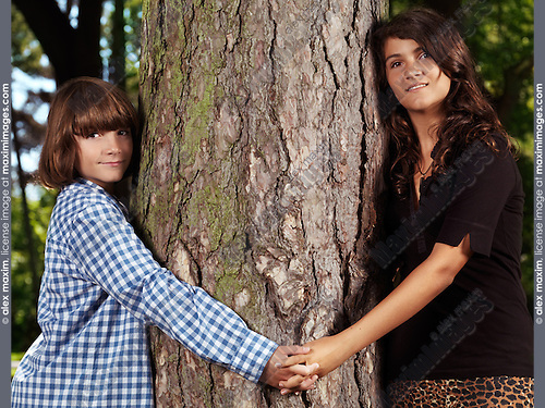 Portrait of two children, brother and sister, 10 and 13, holding hands around a tree.