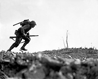 A Marine dashes through Japanese machine gun fire while crossing a draw, called Death Valley by the men fighting there.  Marines sustained more than 125 casualties in eight hours crossing this valley.  Okinawa, May 10, 1945.  Pvt. Bob Bailey.  (Marine Corps)<br /> NARA FILE #:  127-N-120562<br /> WAR &amp; CONFLICT BOOK #:  1229