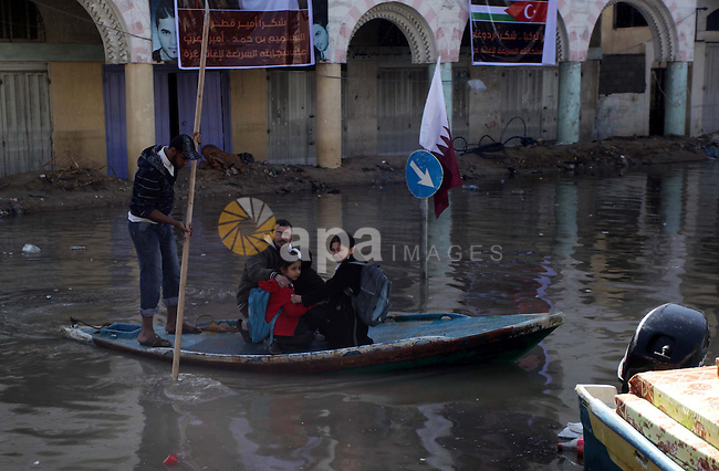 Palestinian rescuer workers help residents in Al Sheikh Redwan area that was flooded in Gaza City, 18 December 2013. Four days of torrential rains in Gaza Strip killed two people and forced the evacuation of more than 5,000 residents from flooded homes, some accessible only by boat, officials said. Photo by Ashraf Amra