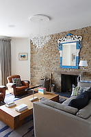 A blue and white metal framed mirror strikes a note of colour on the texture stone wall in the living room