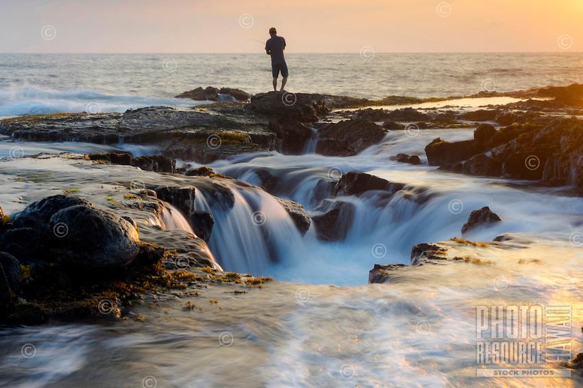 A fisherman with a fishing pole on the rocky coastline near Keahole Point, Big Island.