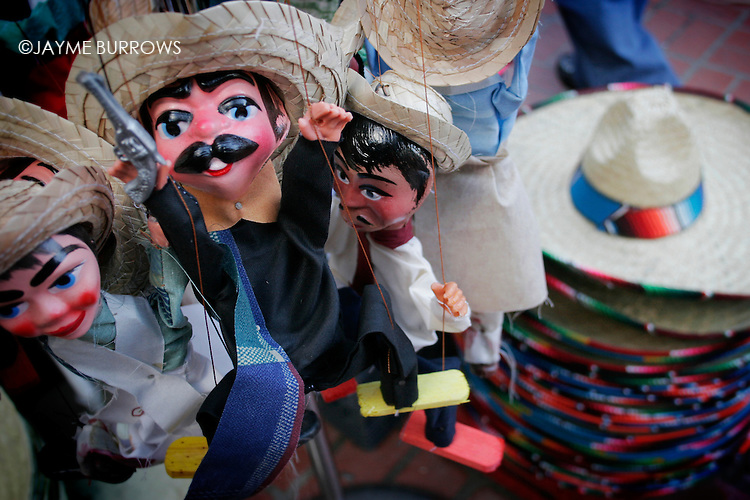 Several puppets at an open air market.