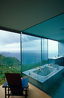 A Rietveld Blue and Red chair is separated from the bathroom  by a glass wall which has a spectacular view of the sea