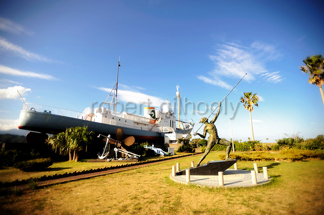A former whaling vessel and a statue of figure in the process of hurling a harpoon stand near the whaling museum in Taiji, Japan on 10 September 2009. .Photographer: Robert Gilhooly....
