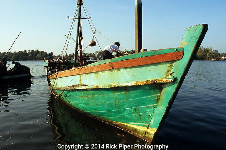 Cham fisherman on colourful fishing boat bringing in the nights catch, at dawn on the Sanke river, Kampot, Cambodia.