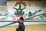 "A Palestinian boy carrying plastic pipes passes by graffiti glorifying the ""Ahmad Aburish Brigades"", the branch of Fatah Al Aqsa Brigades in Khan Yunis. The symbol of the brigades a map of ""Palestine"" (includes the whole Israel) framed by two AK 47 rifles and the Al Aqsa mosque calls by passers to ""fight them"" (meaning Israel). Photo by Quique Kierszenbaum"