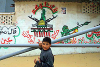 """A Palestinian boy carrying plastic pipes passes by graffiti glorifying the """"Ahmad Aburish Brigades"""", the branch of Fatah Al Aqsa Brigades in Khan Yunis. The symbol of the brigades a map of """"Palestine"""" (includes the whole Israel) framed by two AK 47 rifles and the Al Aqsa mosque calls by passers to """"fight them"""" (meaning Israel). Photo by Quique Kierszenbaum"""