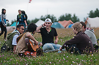 A group of 5 scouts from different countries has found a place at the gras to sit down and play some guitar after the arrival. Photo: Audun Ingebrigtsen/Scouterna